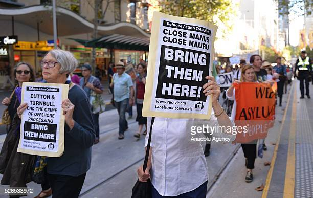 A protestor holds a banner during a protest march demanding that asylum seekers held in off shore detention to be brought to Australia at a rally in...