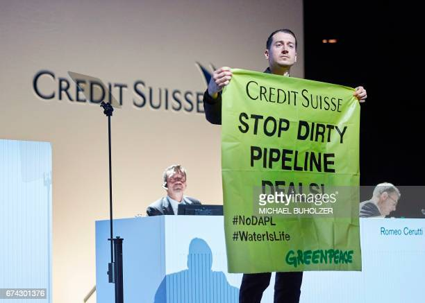 A protestor holds a banner during the annual shareholders' meeting of the Swiss banking group Credit Suisse on April 28 2017 in Zurich / AFP PHOTO /...