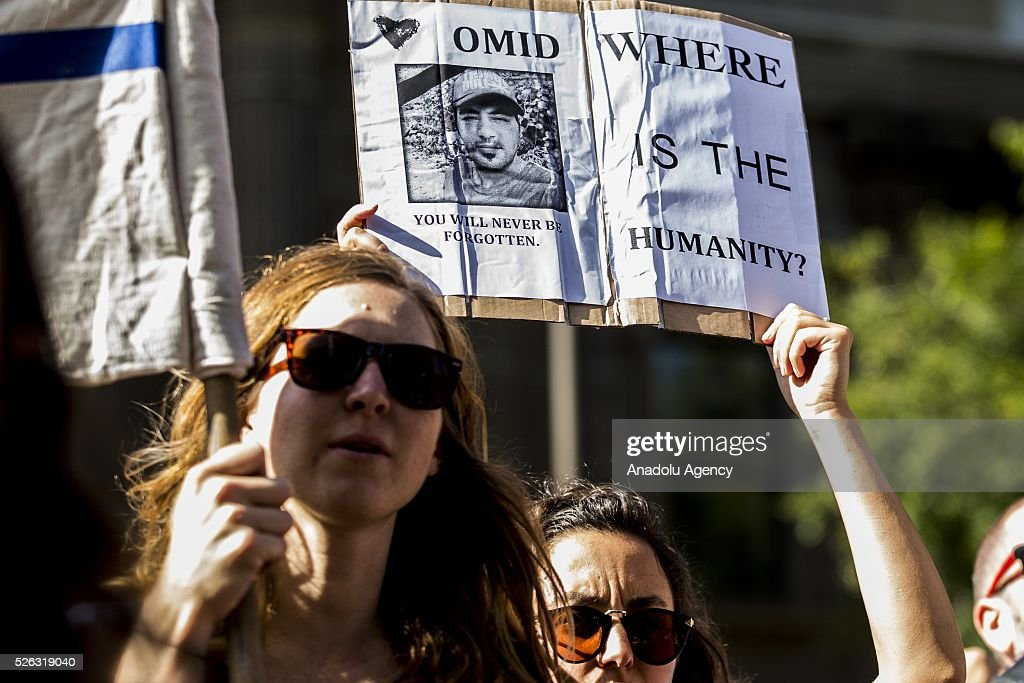 A protestor holds a banner of 23-year-old Iranian known as Omid, an Iranian refugee who set himself on fire at the Nauru detention centre and died in a Brisbane hospital, during a protest demanding that asylum seekers held in off shore detention to be brought to Australia at a rally in Melbourne, Australia on April 30, 2016. Protests have started after The Papua New Guinean Supreme Court ruled that the Australian-run detention centres on Manus Island were illegal and unconstitutional.