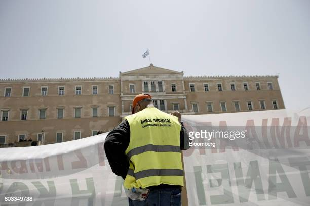 A protestor holds a banner outside the Greek parliament during in a demonstration by municipal contract workers in Athens Greece on Thursday June 29...