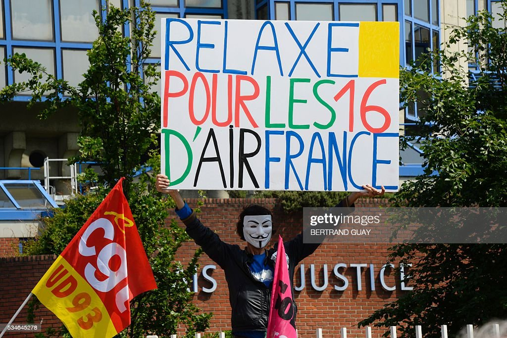 A protestor holds a banner reading 'acquittal for the 16 of Air France' outside the court of Bobigny, northern Paris on May 27, 2016 during the trial of French CGT union's members judged for the episode of the torn shirt, in full showdown initiated by the union with the government on labor law. On October 5, 2015 under the cries of naked, naked and resignation , the Air France human resources director found himself shirtless, tattered shirt during a protest after the announcement of a restructuring of the airline threatening nearly 3,000 jobs.