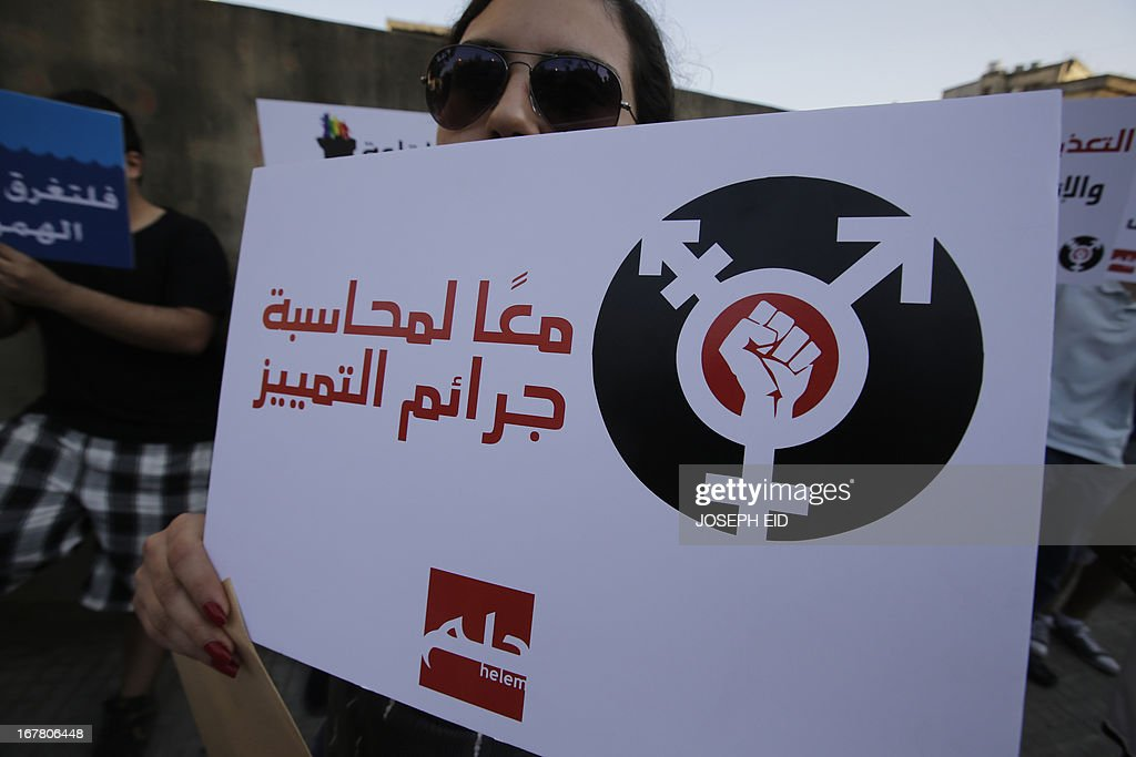 A protestor holds a banner reading in Arabic: 'Together against crimes of discrimination' as she attends an anti-homophobia rally in Beirut on April 30, 2013. Lebanese homosexuals, human rights activists and members from the NGO Helem (the Arabic acronym of 'Lebanese Protection for Lesbians, Gays, Bisexuals and Transgenders') rallied to condemn the arrest on the weekend of three gay men and one transgender civilian in the town of Dekwaneh, east of Beirut, at a nightclub who were allegedly verbally and sexually harassed when they were taken to the municipality headquarters.