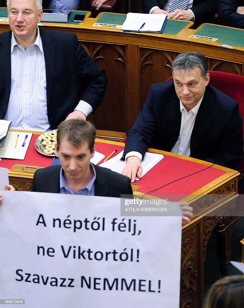 A protestor holds a banner reading 'Vote no' nex to Hungarian Prime Minister Viktor Orban (R) during the parliamentary session to vote on changes to the constitution on March 11, 2013 in Budapest, during the fourth change vote of the basic law, with 265 votes in favour, 11 against and 33 member abstaining. The opposition Socialists party boycotted the vote. The changes, which have also sparked protests in Budapest, include a curb on the power of the constitutional court and reintroduce controversial measures rendered void by the court in recent months.