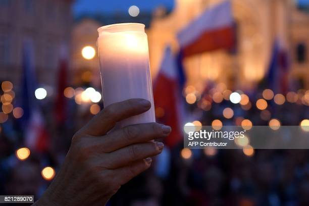 A protestor holds a candle during a demonstration in front of the Polish Supreme Court on July 23 2017 in Warsaw to protest against the new bill...