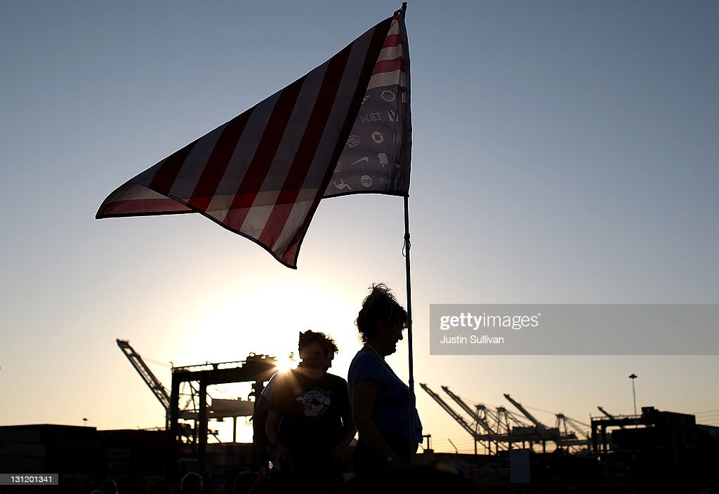 A protestor holds a flag while blocking the entrance to a port at the Port of Oakland during Occupy Oakland's general strike on November 2, 2011 in Oakland, California. Tens of thousands of protestors have tmarched to the Port of Oakland for a general strike organized by Occupy Oakland. Port operations shut down for the evening.