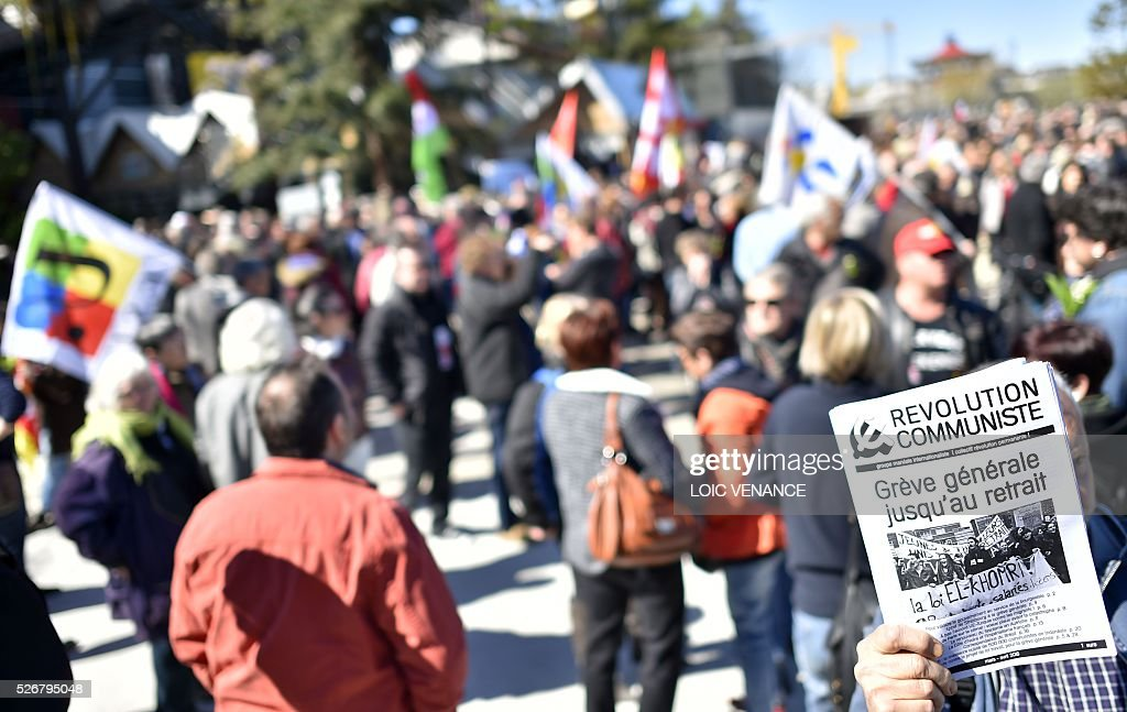 A protestor holds a leaflet reading 'Communist revolution, general strike until the (labour law reform) withdrawal' during the traditional May Day rally in Nantes, western France, on May 1, 2016. / AFP / LOIC
