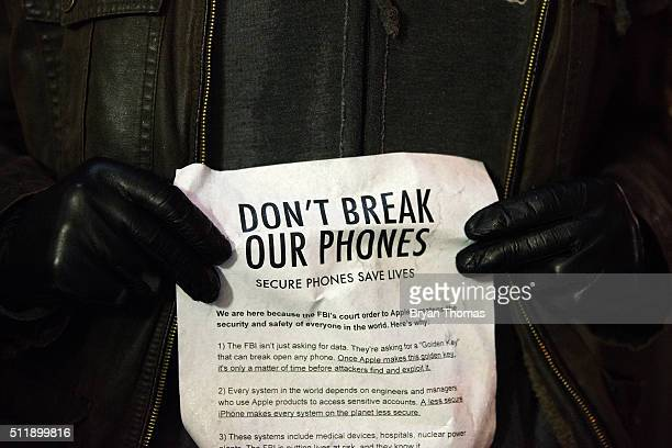 A protestor holds a piece of paper protesting the FBI's recent court order against Apple outside of the the Apple store on 5th Avenue on February 23...