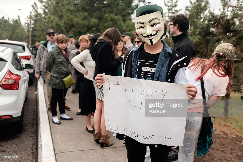 A protestor holds a placard against US Democratic presidential candidate Hillary Clinton on May 5, 2016, in Bend, Oregon. US President Bill Clinton spoke at Central Oregon Community College while campaigning for his wife. / AFP / Rob Kerr