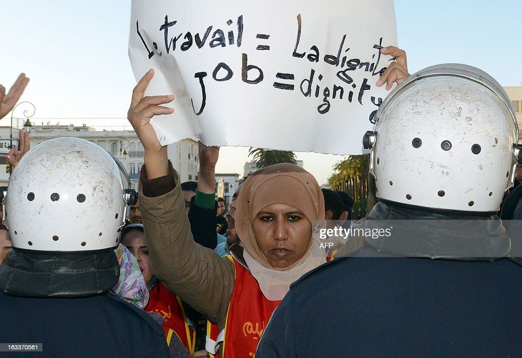A protestor holds a placard reading 'Job = Dignity' during a demonstration to celebrate the International Women's Day on March 8, 2013, in Rabat. The International Women's Day is marked on March 8 every year.