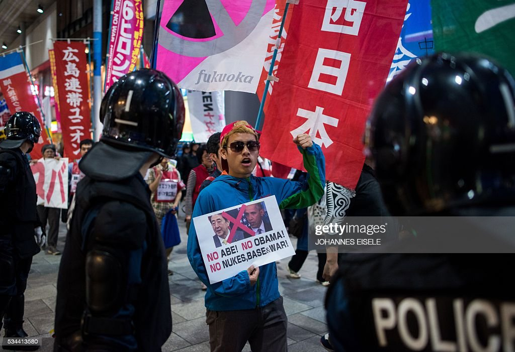 A protestor holds a poster reading 'No Abe! No Obama - We oppose Abe and Obama visit to Hiroshima' during a demonstration next to the Hiroshima Peace Memorial park in Hiroshima on May 26, 2016. US President Barack Obama is set to become the first sitting US president to visit one of the bomb sites when he journeys on May 27, 2016 with Japanese Prime Minister Shinzo Abe to Hiroshima, hallowed ground to Japanese but, for more than 70 years, a no-go zone for 11 of his Oval Office predecessors. / AFP / JOHANNES