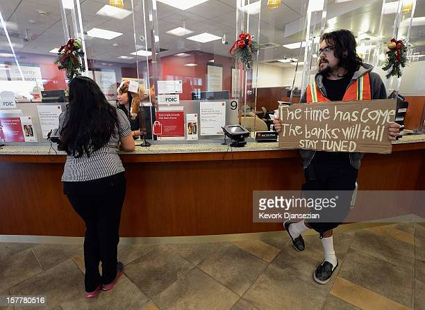 A protestor holds a sign as a bank customers speaks to a bank teller during a demonstration by members of Alliance of Californians for Community...