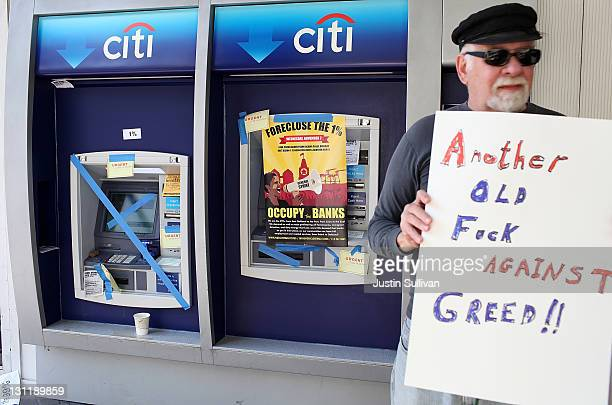A protestor holds a sign in front of a defaced ATM ain front of a CitiBank office during Occupy Oakland's general strike demonstration on November 2...
