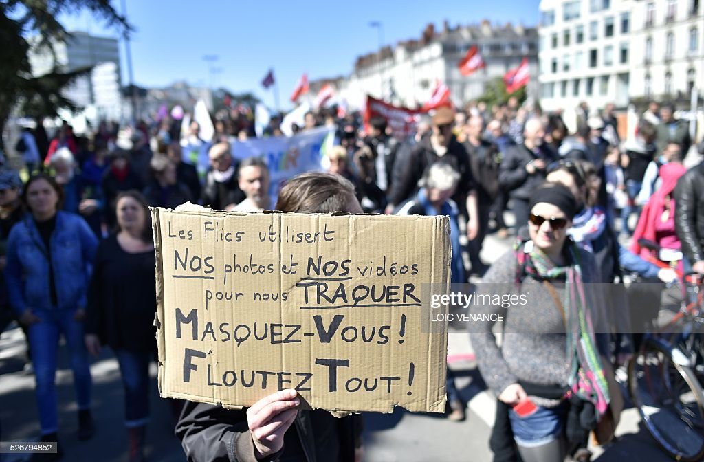 A protestor holds a sign reading 'cops use our pictures and videos to chase us, hide yourself, blur yourself' during the traditional May Day rally in Nantes, western France, on May 1, 2016. / AFP / LOIC