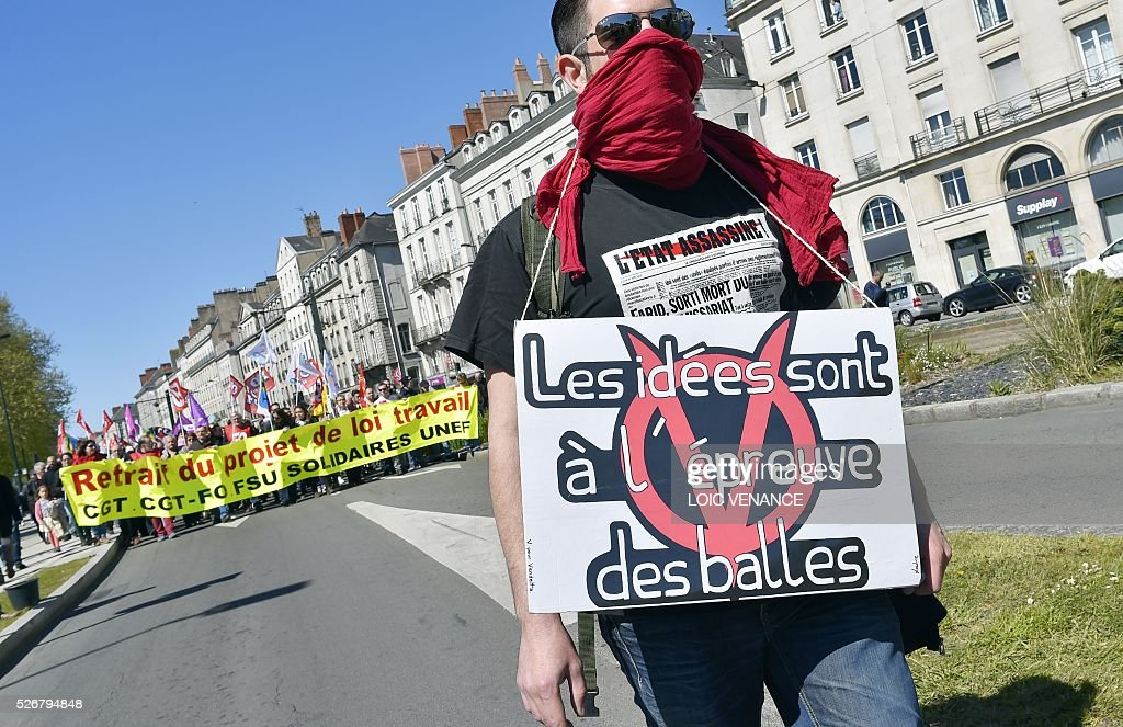 A protestor holds a sign reading 'Ideas stronger than bullets' during the traditional May Day rally in Nantes, western France, on May 1, 2016. / AFP / LOIC