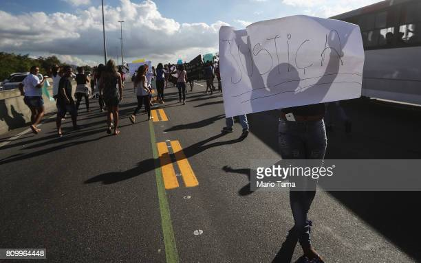 A protestor holds a sign written in Portuguese reading 'Justice' as others march along a highway following the funeral of Vanessa dos Santos who was...