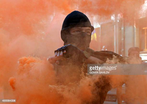 A protestor holds a smoke bomb during a demonstration outside the President Palace in Kiev on September 17 2014 Activists from farright nationalist...