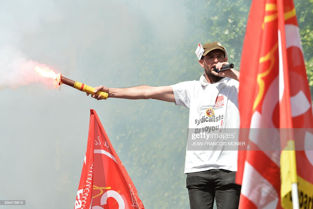 A protestor holds a smoke grenade during a protest against the government's labour market reforms in Rennes, northwestern France, on May 26, 2016. The French government's labour market proposals, which are designed to make it easier for companies to hire and fire, have sparked a series of nationwide protests and strikes over the past three months.