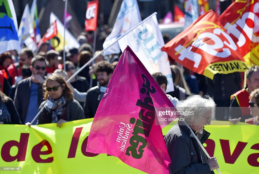 A protestor holds a union flag during the traditional May Day rally in Nantes, western France, on May 1, 2016. / AFP / LOIC