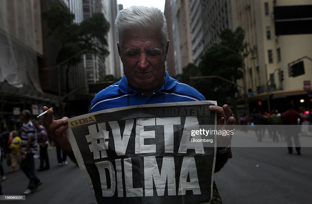 A protestor holds a 'Veta Dilma' sign during a demonstration in Rio de Janeiro, Brazil, on Monday, Nov. 26, 2012. Tens of thousands of residents in Rio de Janeiro attended a rally today urging Brazilian President Dilma Rousseff to veto an oil royalties law that the state's governor claimed will derail the 2016 Olympics. Photographer: Dado Galdieri/Bloomberg via Getty Images