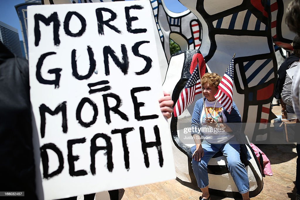 A protestor holds American flags during a demonstration in favor of gun regulation outside of the 2013 NRA Annual Meeting and Exhibits at the George R. Brown Convention Center on May 4, 2013 in Houston, Texas. More than 70,000 peope are expected to attend the NRA's 3-day annual meeting that features nearly 550 exhibitors, gun trade show and a political rally. The Show runs from May 3-5.