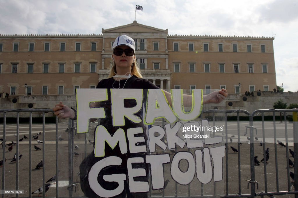 A protestor holds banner which reads 'Frau Merkel Get Out' in front of Parliament on October 9, 2012 in Athens, Greece. Up to 7,00 police officers are said to be on duty ahead of the German Chancellor Angela Merkel's one day visit to Athens, which is her first since the Eurozone crisis erupted almost three years ago .