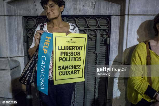 A protestor holds banners during a candlelit vigil to demand the release of imprisoned seperatist leaders Jordi Sanchez head of the Catalan National...