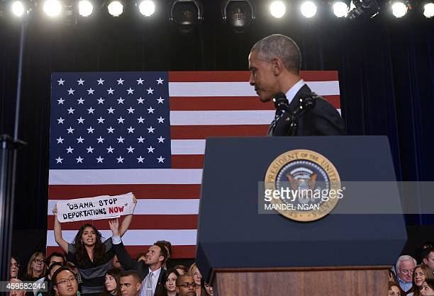 A protestor holds up a banner as a guest beside her reaches to pull it away as US President Barack Obama speaks on immigration reform at the...