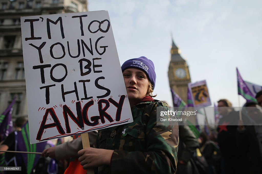 A protestor holds up a banner reading 'I'm too young to be this Angry' while taking part in a TUC march in protest against the government's austerity measures on October 20, 2012 in London, England. Thousands of people are taking part in the Trades Union Congress (TUC) organised anti-cuts march that ends with a rally in Hyde Park, where Labour leader Ed Miliband is scheduled to address the demonstrators.