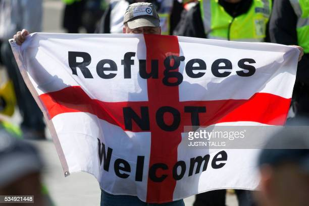 A protestor holds up a flag that reads 'Refugees Not Welcome' during a demonstration by far right protesters in the town of Dover in south east...