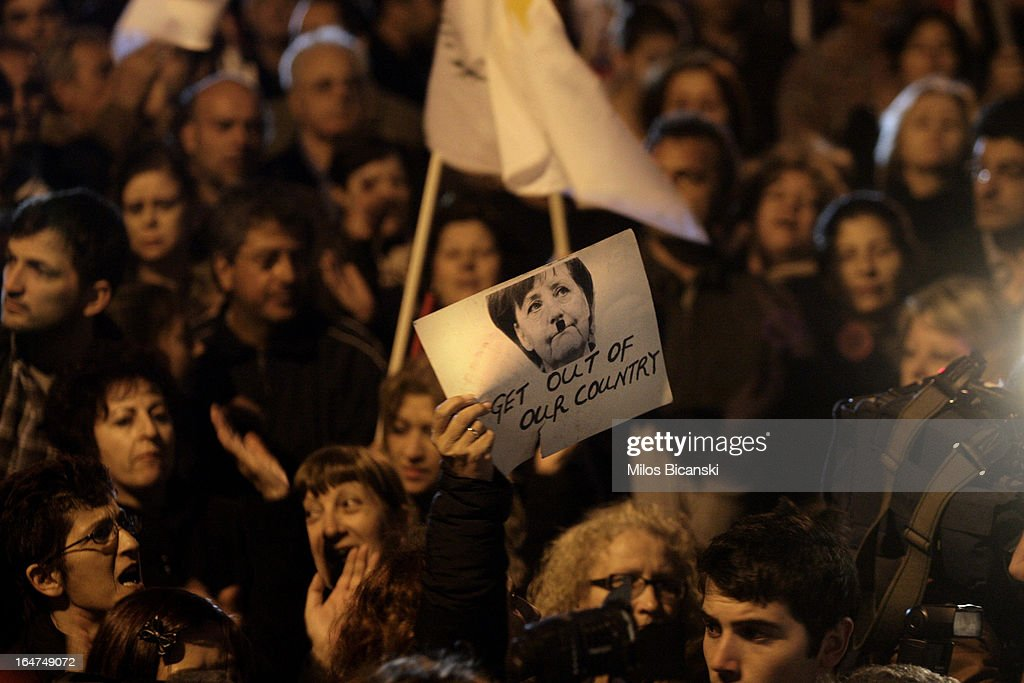 A protestor holds up a sign depicting German Chancellor Angela Merkel during a protest against austery measures and the Troika on March 27, 2013 in Nicosia, Cyprus. After days of negotiation, Eurozone finance ministers have agreed terms for a 10 billion euro bailout deal, which aims to prevent the collapse of Cypriot banks and ensure that Cyprus remain in the Eurozone. Yiannis Kyrpi, the chief executive of Bank of Cyprus, has been removed from his post following the agreement, whilst banks remain closed to the public and are expected to enforce withdrawal restrictions when they re-open.