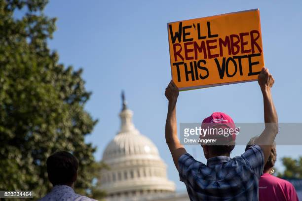 A protestor holds up a sign during a rally against the GOP health care plan on Capitol Hill July 26 2017 in Washington DC GOP efforts to pass...