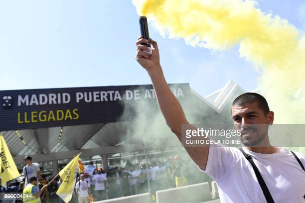 A protestor holds up a smoke canister as taxi drivers gather during a strike action held between Atocha Train station to Neptuno Square in Madrid on...