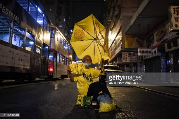 TOPSHOT A protestor holds up a yellow umbrella as she protests in a street in Hong Kong early on November 7 2016 Hong Kong police used pepper spray...