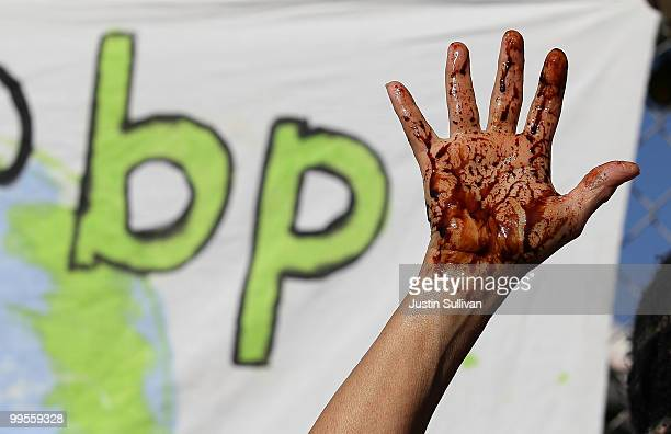 A protestor holds up her hand that is covered with simulated oil during a demonstration outside of a building that is being constructed on the UC...