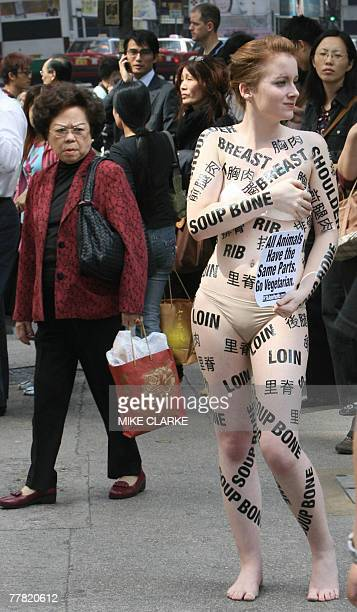 A PETA protestor in a body suit holds a 'Naked Woman Demonstration All Animals Have The Same Parts' at a busy intersection in the Causeway Bay...