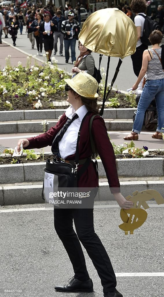 A protestor in costume hands out fake notes during a demonstration against proposed government labour and employment law reforms on May 26, 2016 in Toulouse. Workers at nuclear power stations in France were set to go on strike May 26, joining a growing protest movement against controversial labour market reforms that has already severely disrupted fuel supplies. Unions have called for fresh rallies in cities across France on May 26, the latest bout of social unrest that started around three months ago and has frequently turned violent. PAVANI