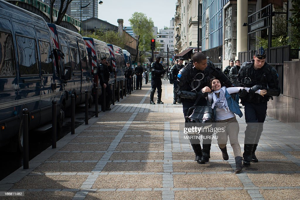 A Protestor is arrested during a demonstration to call for the release of two Palestinian soccer players in an Israeli jail, on April 17, 2013 in front of the French football Federation (FFF) in Paris. AFP PHOTO MARTIN BUREAU