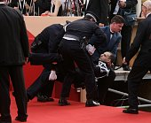 A protestor is been removed by the gendarmes from the red carpet during 'The Da Vinci Code' World Premiere Opening Gala at the Palais during the 59th...