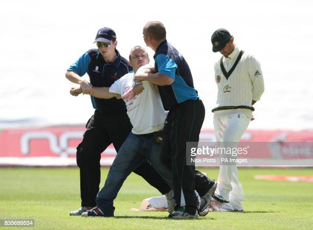 A protestor is carried from the field of play by security officials as Australia captain Ricky Ponting kicks away a banner left behind during day...