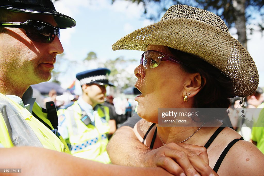 A protestor is held back by police as New Zealand Prime Minister John Key meets members of the public at The Big Gay Out on February 14, 2016 in Auckland, New Zealand.