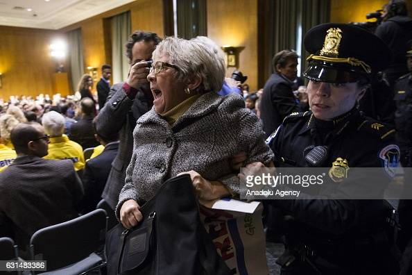 A protestor is led out by Capitol Police after interrupting the confirmation hearing of Rex Tillerson former CEO of ExxonMobile by the Senate Foreign...