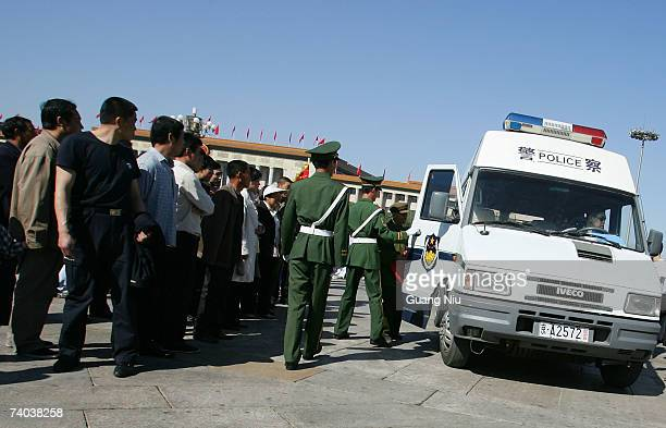A protestor is put into a police van in Tiananmen Square as thousands of people visit the square to mark May Day on May 1 2007 in Beijing China 50...