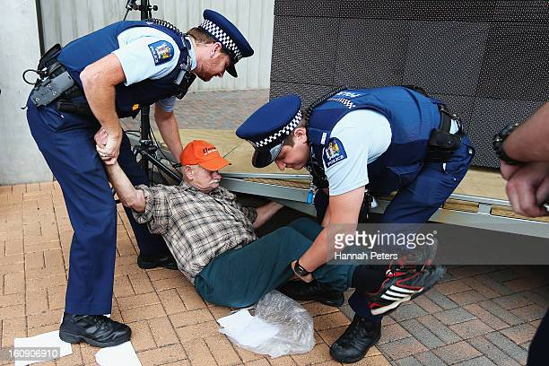 A protestor is removed by police outside the Auckland Cathedral of the Holy Trinity in Parnell on February 8 2013 in Auckland New Zealand Hundreds...