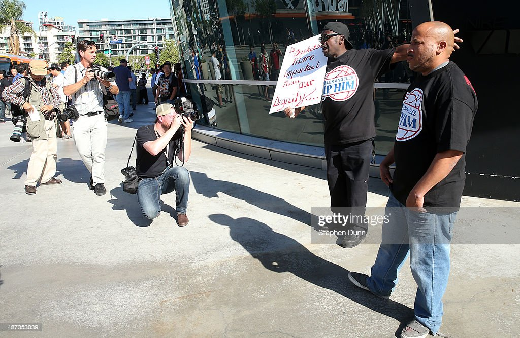 Protestor Jerry Carr (second from right) holds a sign as photographers take pictures in the wake of Los Angeles Clippers owner Donald Sterling before Game Five of the Western Conference Quarterfinals during the 2014 NBA Playoffs at Staples Center on April 29, 2014 in Los Angeles, California.