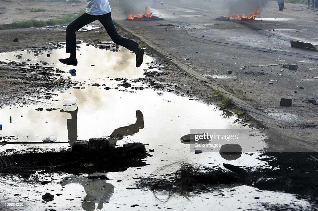 A protestor jumps over a puddle of water on January 21, 2013, in Sasolburg, South Africa. Protesting broke out as a result of the announcement of the intention to integrate municipal systems from Sasol to Parys.