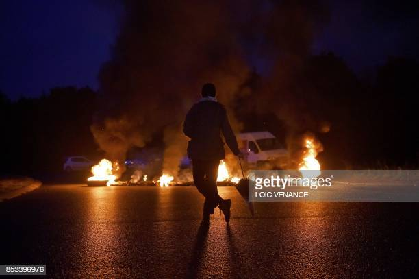 TOPSHOT A protestor looks at a fire displayed on a traffic circle as union trade members block trucks on September 25 2017 in Donges western France...