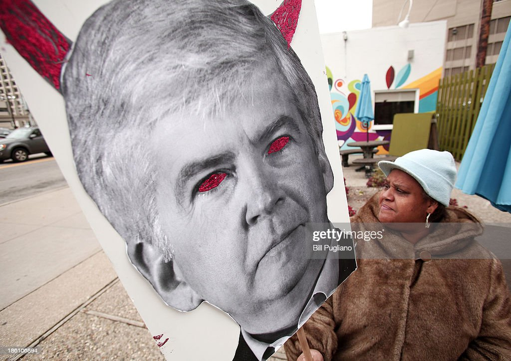 Protestor Maria Richardson of Detroit, Michigan holds a sign that depicts Michigan Gov. Rick Snyder as a devil during a rally in front of the U.S. Courthouse in Detroit where Detroit's bankruptcy eligibility trial is taking place October 28, 2013 in Detroit, Michigan. Michigan Gov. Rick Snyder is expected to testify today at the trial. A federal judge will decide if the City of Detroit is eligible to be in bankruptcy court.