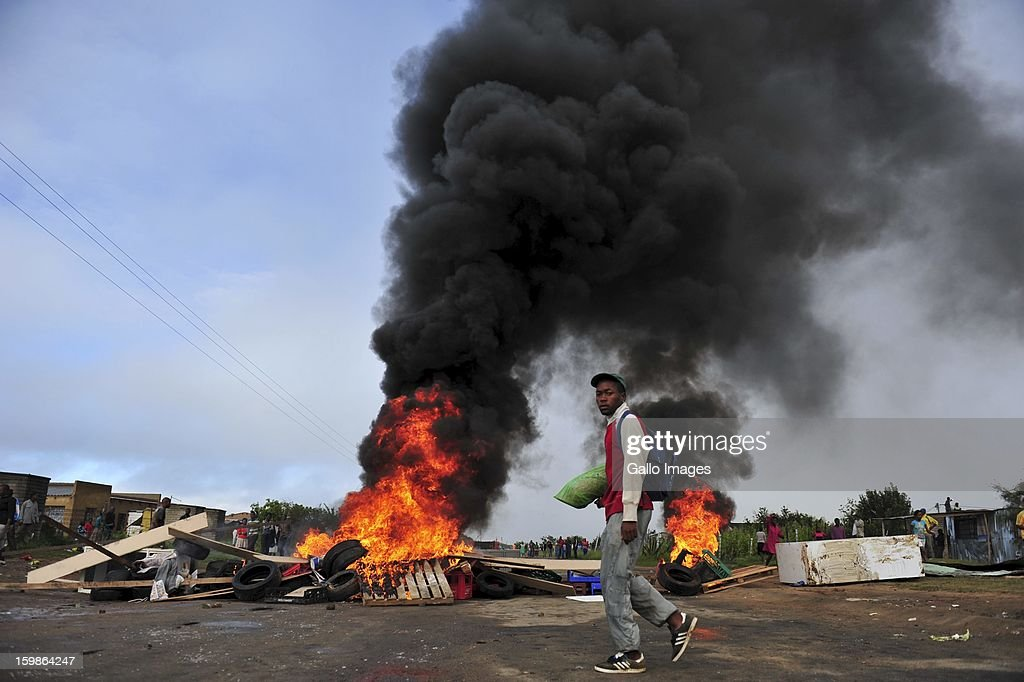 A protestor passing a heap of burning tires on January 21, 2013, in Sasolburg, South Africa. Protesting broke out as a result of the announcement of the intention to integrate municipal systems from Sasol to Parys.