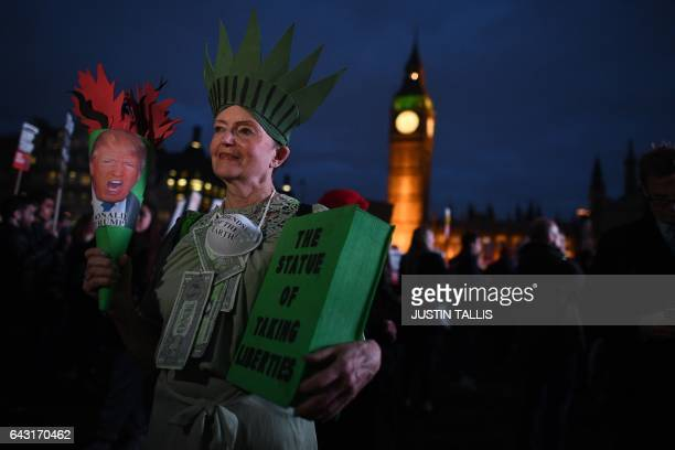 TOPSHOT A protestor poses for a picture at an antiTrump protest near the Houses of Parliament in London on February 20 as parliament debates whether...