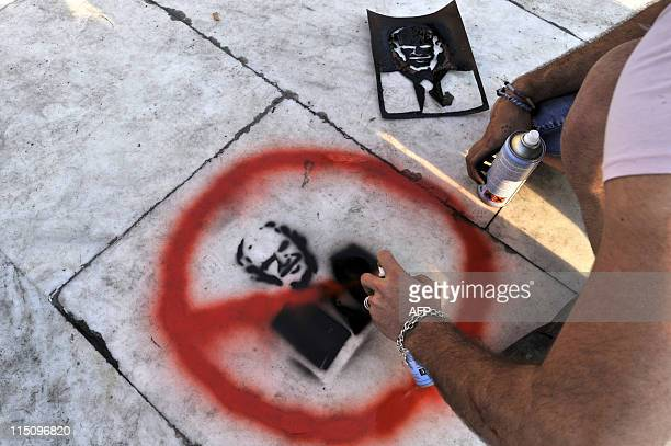 A protestor puts a red circle around and cross through a stencil depicting the Greek Prime Minister George Papandreou on the pavement in front of the...